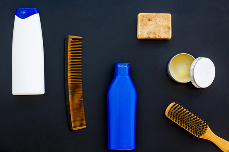Shampoo bottle and comb for man care in barbershop on dark background top view mockup