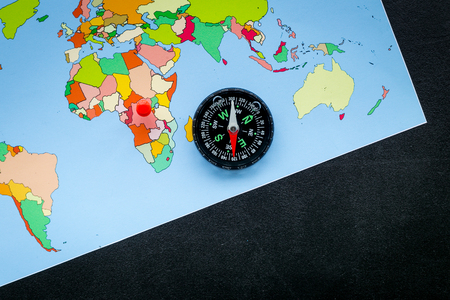 Travel direction and trip planning concept with compass and map of the world on black desk background top view