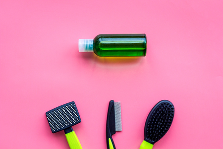 Care about pet with brushes and grooming equipment on pink background top view mockup