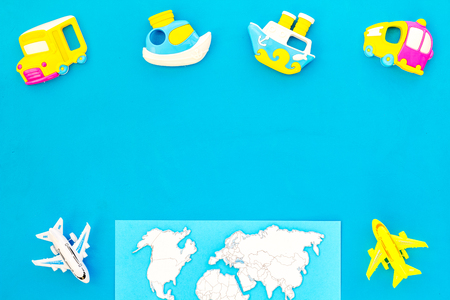 Accessories for traveling with children, map and toys on blue background top view mock-up