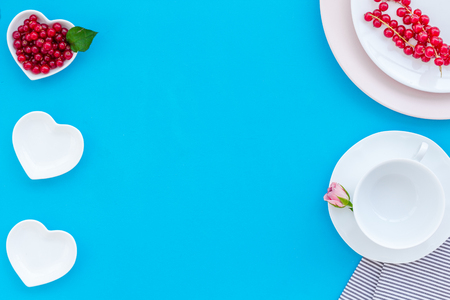 Set-up table with plates, wineberry and flower on blue background top view mock-up