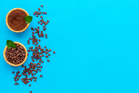 Coffee concept. Roasted beans, ground coffee on blue background top view copy space Stock Photo