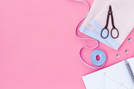 Tailor work place with thread, scissors, fabric. Sewing as hobby. Pink background top view space for text Imagens