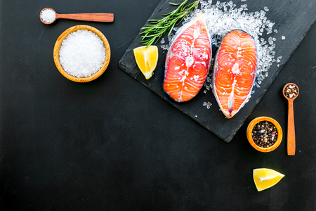 Fresh salmon steak with spices, rosemary, lemon for cooking healthy food on dark background top view mock-up Imagens