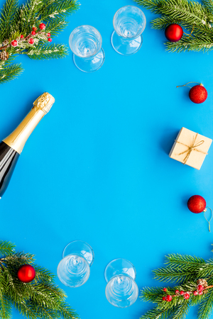 Spruce, champagne bottle, gift and glasses for Christmas celebration on blue background top view mockup Stock Photo
