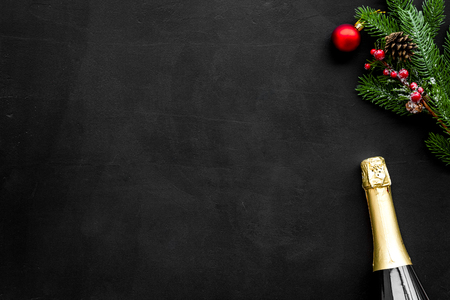 New year and Christmas party with spruce, champagne bottle on black background top view space for text