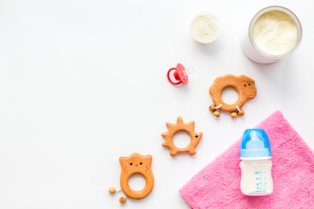 Toys for newborn baby set with plastic rattle and milk in bottle on white background flat lay space for text