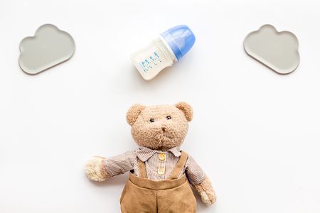 Craft toys for kids. Handmade teddy bear and baby bottle with milk. White background top view Stockfoto