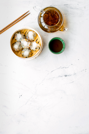 Chinese steamed dumplings Dim Sum in bamboo steamer with tea on marble background top view mock up Stock Photo