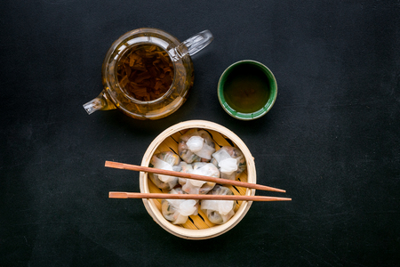 Dim sums with sticks and herbal tea in Chinese restaurant on black background top view Stock Photo