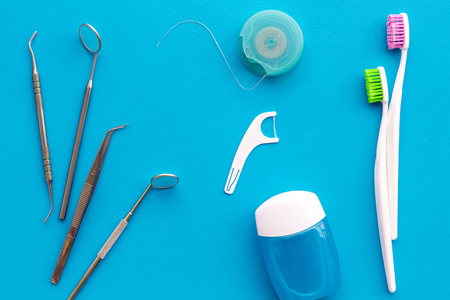 Tooth care with toothbrush, dental floss and dentist instruments. Set of cleaning products for teeth on blue background top view
