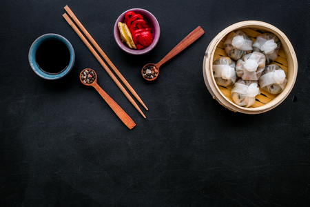 Chinese food set with dim sum, sticks and tea on black background top view copy space Stock Photo