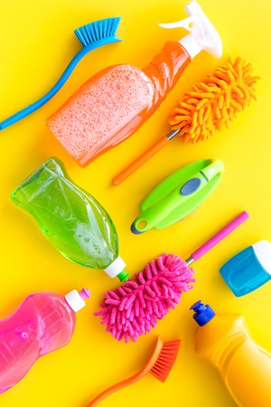 Housecleaning with detergents, soap, cleaners and brush in plastic bottles on yellow background top view mockup Stockfoto