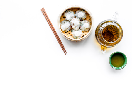 Dim sums with sticks and herbal tea in Chinese restaurant on white background top view mockup