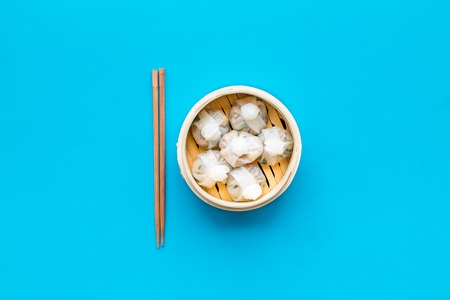 Dim sums with red pepper and vegetables with sticks in Chinese restaurant on blue background top view Stock Photo