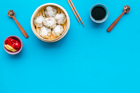 Chinese steamed dumplings Dim Sum with sweet paper and spices in bamboo steamer on blue background top view mock up