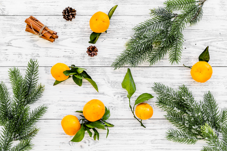 Pile of tangerines, fir tree and cinnamon for New Year and Christmas celebration on white wooden background top view