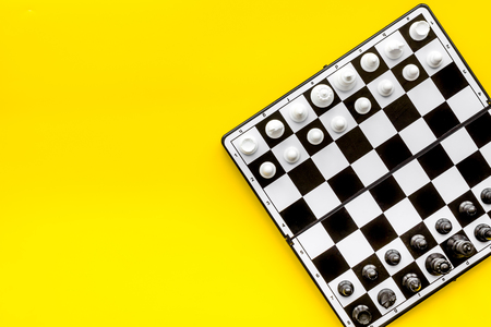Chess game concept. Chess board with figures on yellow background top view space for text