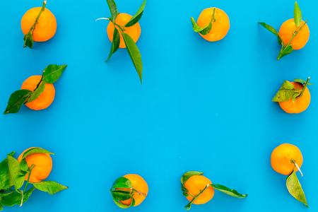 Branch of mandarins for New Year and Christmas celebration on blue background top view mockup