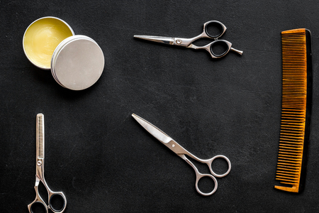 Instruments of male hairdresser barbershop top view on dark background