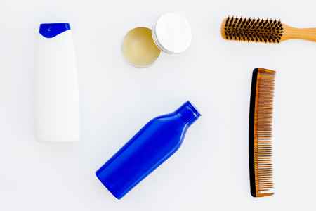 Barber workspace with equipment. Shampoo bottle and comb on white background top view space for text