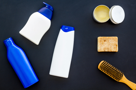 Male care set for barbershop with shampoo bottle and comb on dark background top view mock-up