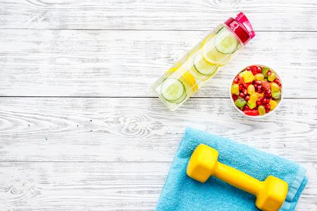Estilo de vida saludable, hábitos saludables. Agua de desintoxicación, ensalada de frutas, mancuernas de equipamiento deportivo en el espacio de copia de vista superior de fondo de madera blanca