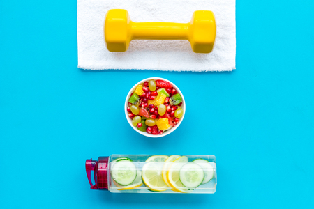 Healthy lifestyle, healthy habits. Detox water, fruit salad, sport equipment dumbbells on blue background top view 版權商用圖片