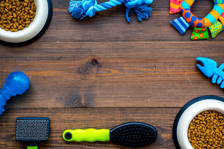 Care about pet with brushes, food and grooming equipment wooden background top view mockup