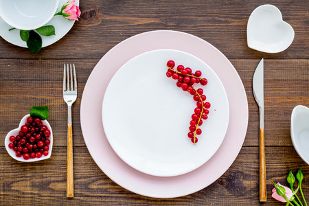 Table setting with plates, wineberry, fork, knife and flower on wooden kitchen background top view