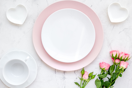 Set-up table with plates, heart-shaped saucer and flower on white background top view mock-up