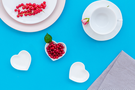 Table setting with plates, wineberry and flower on blue kitchen background top view