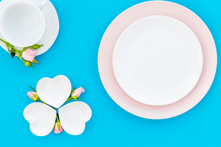 Elegant table setting with white and rose plates and floral decor on blue background top view mock up Stock Photo