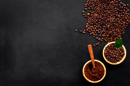 Coffee concept. Roasted beans, ground coffee on black background top view copy space 版權商用圖片