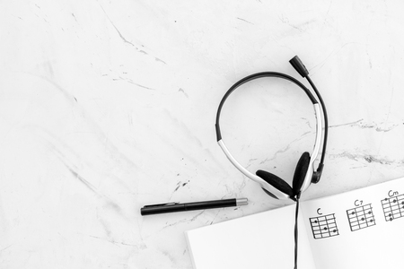 Musician work set with notes and headphones marble table background top view copy space Stock Photo - 114133484