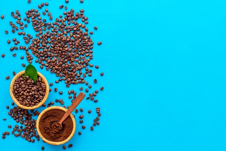 Brown roasted coffee beans scattered on blue background top view mockup Stock Photo