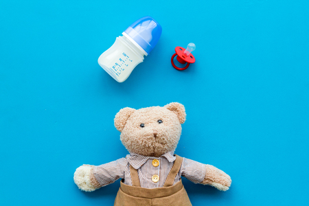 Craft toys for kids. Handmade teddy bear, dummy and baby bottle with milk. Blue background top view Stock Photo - 114133636