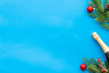 New year and Christmas party with spruce, champagne bottle and glasses on blue background top view space for text