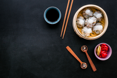Dinner in Chinese restaurant with dim sum, sticks and tea on black background top view space for text