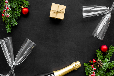 New year design with spruce, champagne bottle, gift and glasses black table background top view space for text