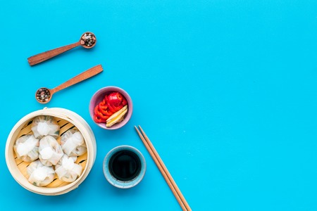 Dinner in Chinese restaurant with dim sum, sticks, spices and tea on blue background top view space for text
