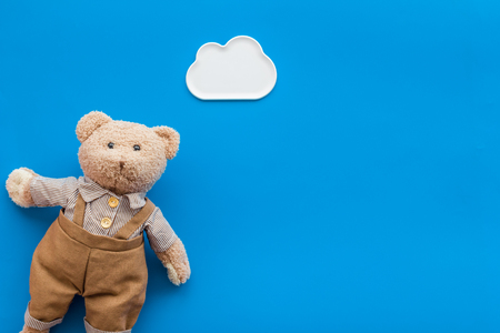 Toys for newborn baby set with teddy bear and clouds on blue background flat lay space for text