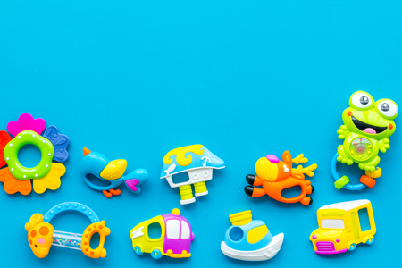 Baby care with craft toys for newborn. Rattle. Blue background top view copy space