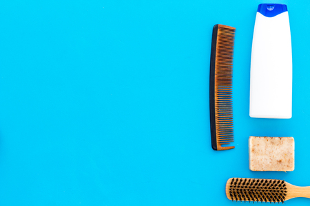 Instruments of male hairdresser with shampoo and comb in barbershop top view on light blue background mock up
