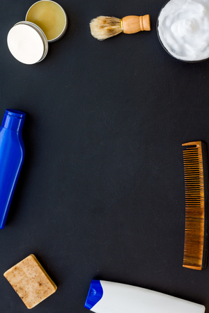 Male care set for barbershop with shampoo bottle and comb on dark desk background top view mock-up
