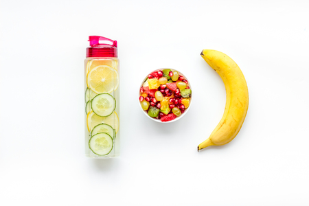Weight loss concept. Fruit salad near fruit lemon and cucumber water on white background top view. Stock Photo - 114133684