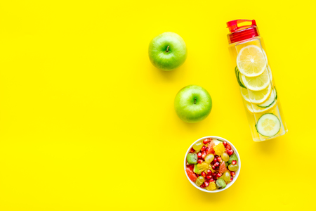Diet rich in fruits. Slimming diet. Fruit salad near fruit lemon and cucumber water on yellow background top view.
