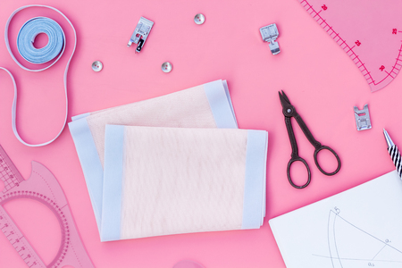 Tailor work place with thread, scissors, fabric. Sewing as female hobby. Pink background top view space for text