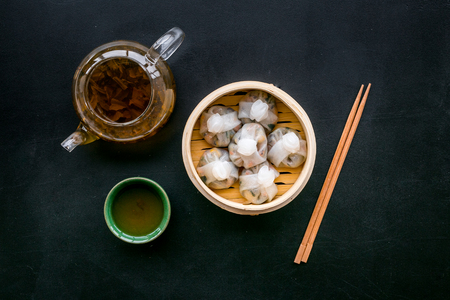 Dim sums with sticks and herbal tea in Chinese restaurant on black table background top view