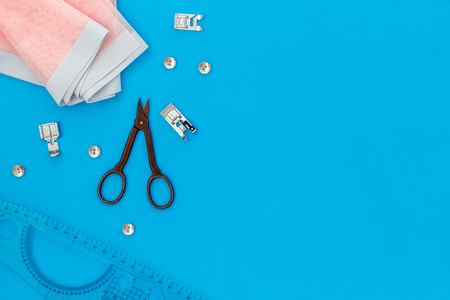 Tailor shop with thread, scissors, fabric. Sewing as hobby. Blue background top view mockup